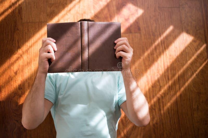 Άτομο που διαβάζει την παλαιά εκμετάλλευση βιβλίων βιβλίων με σκληρό εξώφυλλο στα χέρια του, στο καφετί πάτωμα στο σπίτι Εσωτερικ στοκ εικόνα