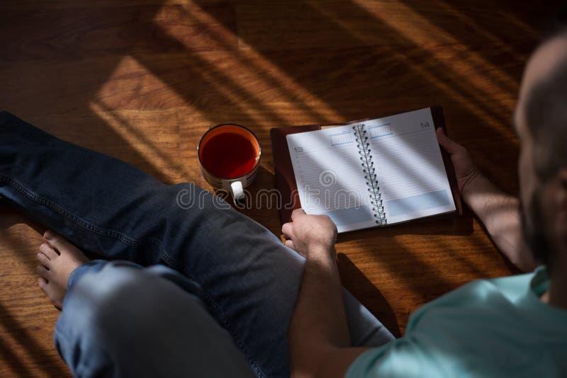 Άτομο που διαβάζει την παλαιά εκμετάλλευση βιβλίων βιβλίων με σκληρό εξώφυλλο στα χέρια του, στο καφετί πάτωμα στο σπίτι Εσωτερικ στοκ φωτογραφίες