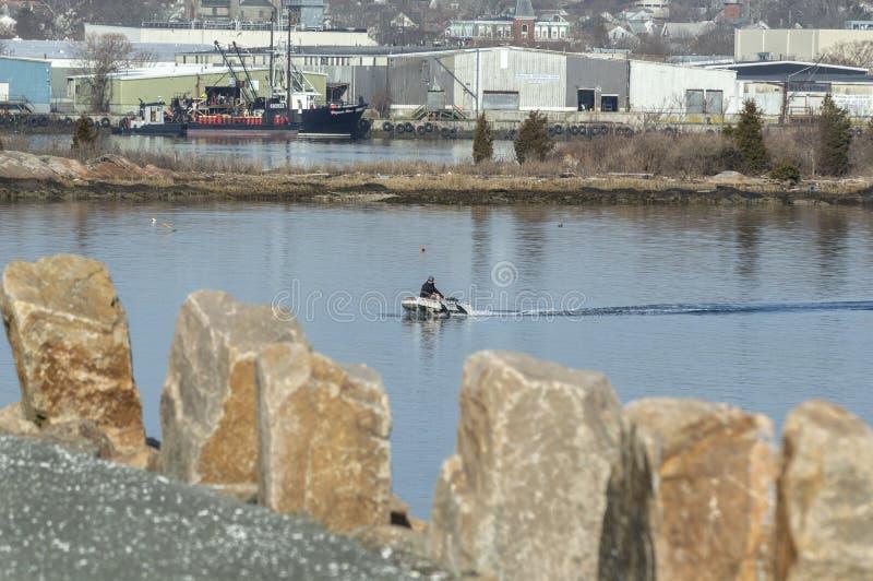 Άτομο που διασχίζει τον ποταμό Acushnet την πρώιμη άνοιξη στη μικρή διογκώσιμη βάρκα στοκ φωτογραφίες