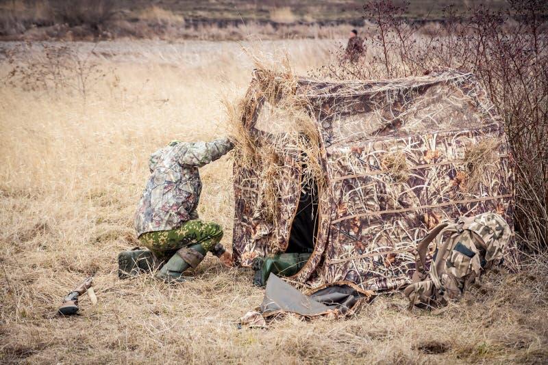 Άτομο που εγκαθιστά τη σκηνή κυνηγιού στον αγροτικό τομέα στοκ φωτογραφία με δικαίωμα ελεύθερης χρήσης