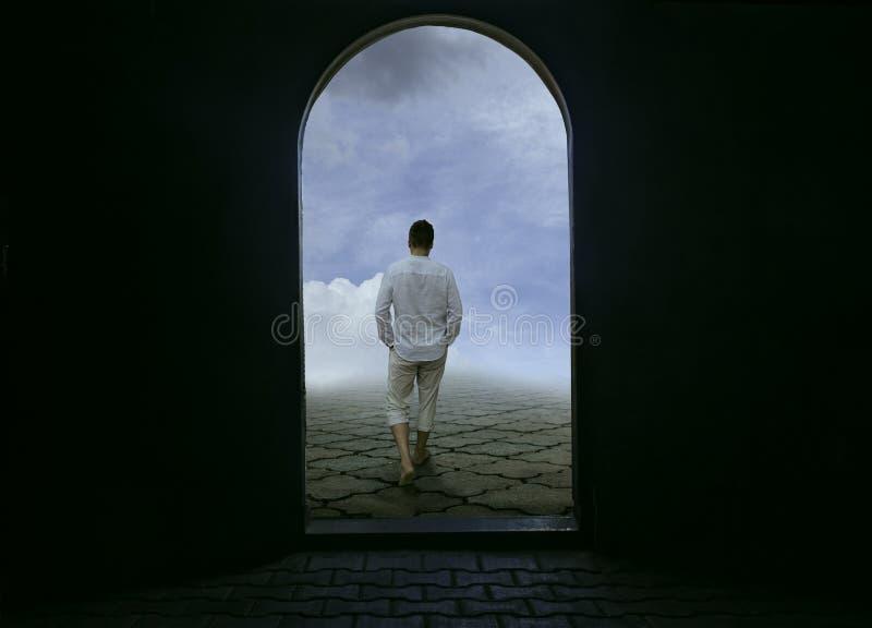 Άτομο που εγκαταλείπει τη σκοτεινή φυλακή στο φωτεινό μέλλον στοκ φωτογραφία
