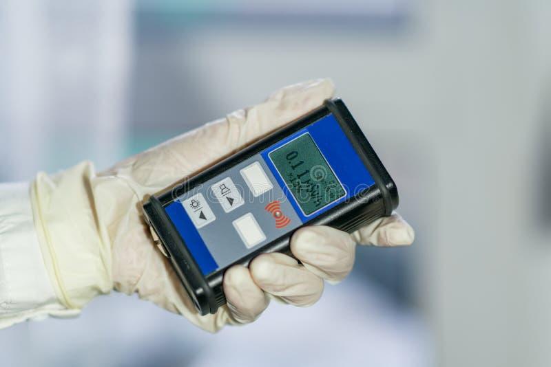 Άτομο που ελέγχει την ακτινοβολία με geiger το μετρητή στοκ φωτογραφία