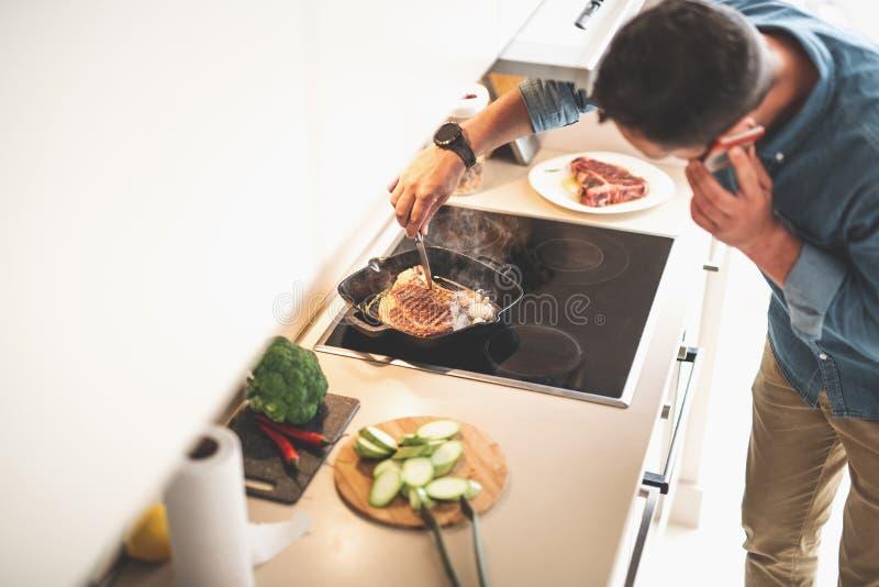 Άτομο που ελέγχει την ετοιμότητα της μπριζόλας βόειου κρέατος με το μαχαίρι μιλώντας στο κινητό τηλέφωνο στοκ φωτογραφίες