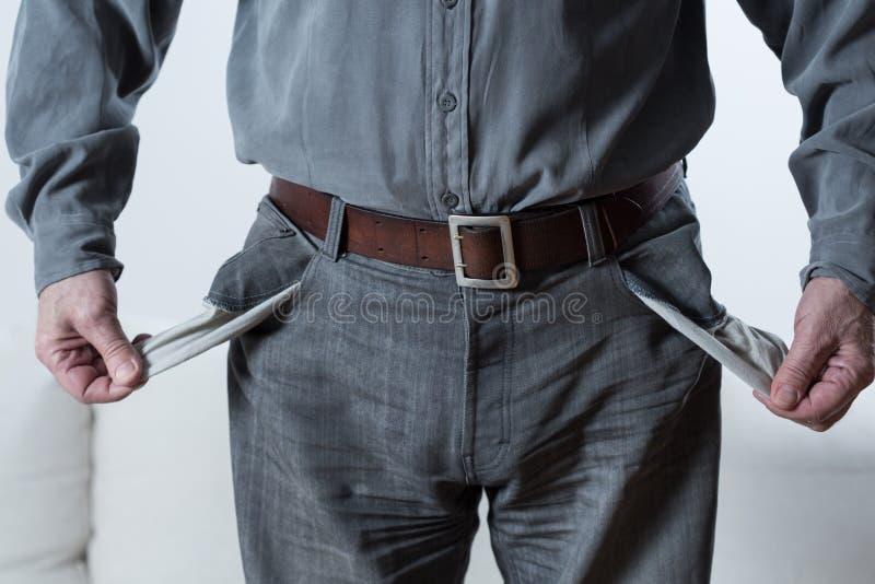 Άτομο που εμφανίζει κενές τσέπες στοκ φωτογραφία
