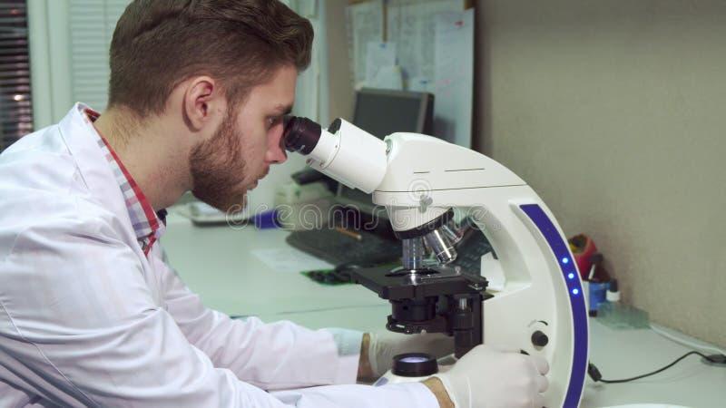 Άτομο που εξετάζει μέσω του μικροσκοπίου το εργαστήριο στοκ φωτογραφία