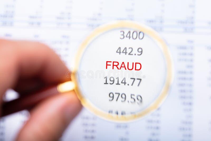 Άτομο που εξετάζει την απάτη Word στην οικονομική έκθεση στοκ εικόνα με δικαίωμα ελεύθερης χρήσης