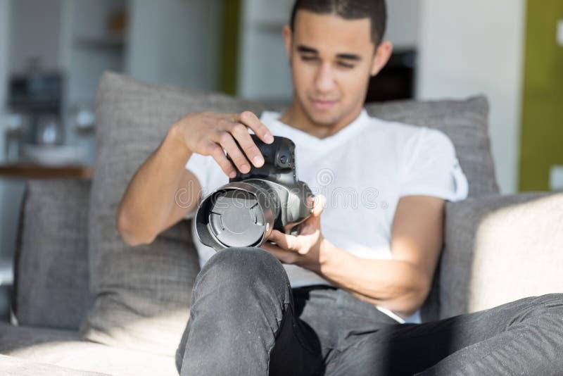 Άτομο που εξετάζει τη κάμερα DSLR καθμένος στο εσωτερικό στοκ φωτογραφία με δικαίωμα ελεύθερης χρήσης