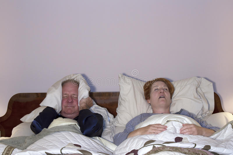 Άτομο που εξετάζει τη σύζυγο Snoring στοκ φωτογραφίες