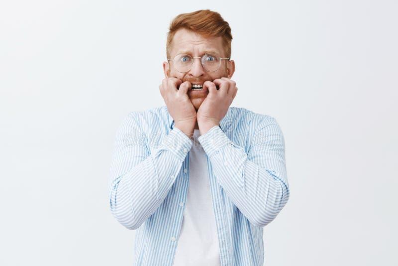 Άτομο που εξετάζει το εύθραυστο πράγμα για να πέσει περίπου Πορτρέτο του νευρικού redhead ώριμου τύπου με τη σκληρή τρίχα, δάγκωμ στοκ φωτογραφίες