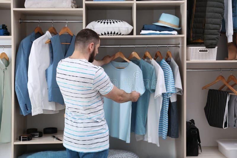 Άτομο που επιλέγει την εξάρτηση από το μεγάλο ντουλάπι ντουλαπών με τα ενδύματα και την εγχώρια ουσία στοκ φωτογραφία