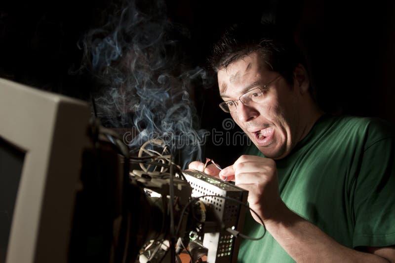 Άτομο που επισκευάζει τον υπολογιστή στην πυρκαγιά στοκ εικόνες