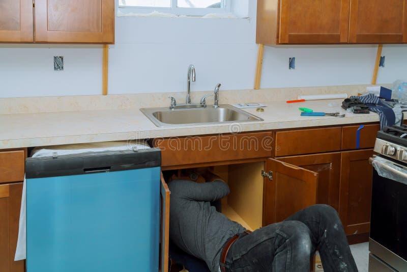 Άτομο που επισκευάζει το σωλήνα νεροχυτών στους σωλήνες συναρμολογήσεων υδραυλικών κουζινών στοκ εικόνες