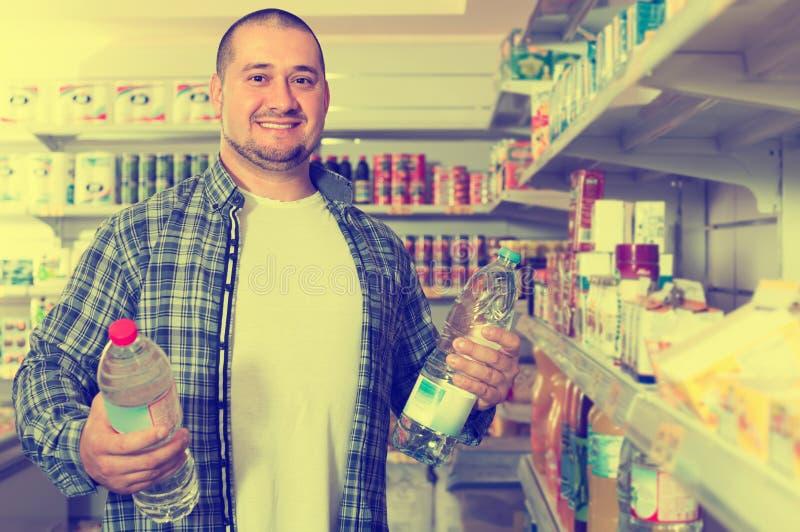 Άτομο που επιλέγει το μεταλλικό νερό στο παντοπωλείο στοκ φωτογραφία