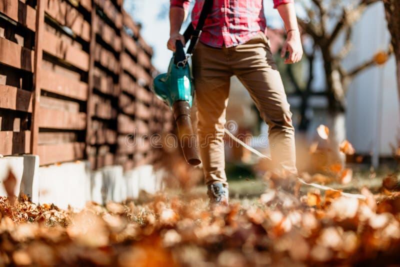 Άτομο που εργάζεται με τον ανεμιστήρα φύλλων, καθαρισμός φθινοπώρου στον κήπο στοκ φωτογραφίες
