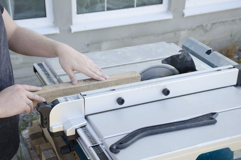 Άτομο που εργάζεται με το ξύλο πεύκων να πριονίσει τον κυκλικό πίνακα στοκ εικόνα με δικαίωμα ελεύθερης χρήσης