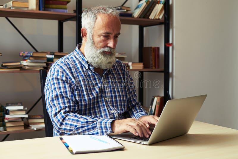 Άτομο που εργάζεται με το lap-top στην αρχή στοκ φωτογραφίες με δικαίωμα ελεύθερης χρήσης