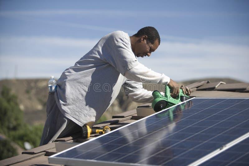 Άτομο που εργάζεται στην ηλιακή ξυλεπένδυση στη στέγη στοκ εικόνες