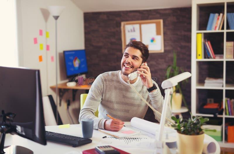 Άτομο που εργάζεται στον υπολογιστή που μιλά στο τηλέφωνο γραμμών εδάφους στοκ εικόνες με δικαίωμα ελεύθερης χρήσης