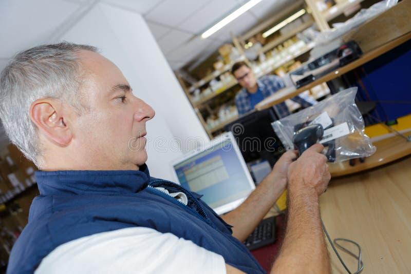 Άτομο που εργάζεται στο γραφείο στο γραμμωτό κώδικα ανίχνευσης αποθηκών εμπορευμάτων στοκ εικόνα με δικαίωμα ελεύθερης χρήσης
