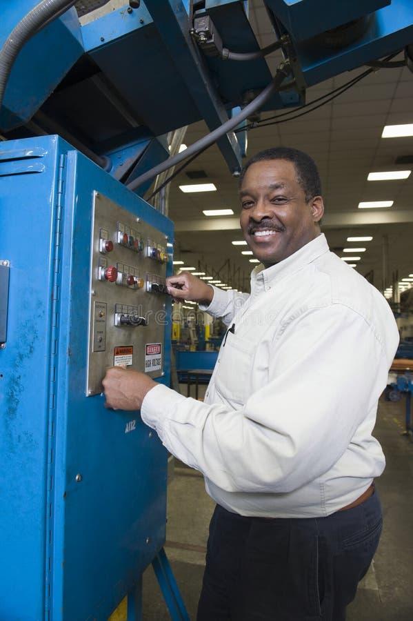 Άτομο που εργάζεται στο πίνακα ελέγχου στο εργοστάσιο στοκ φωτογραφία