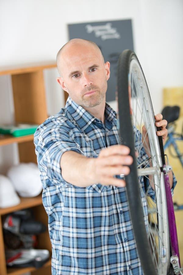 Άτομο που ευθυγραμμίζει τη ρόδα ποδηλάτων στοκ φωτογραφίες