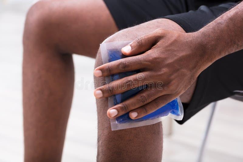 Άτομο που εφαρμόζει το πακέτο πηκτωμάτων πάγου στο γόνατό του στοκ εικόνα