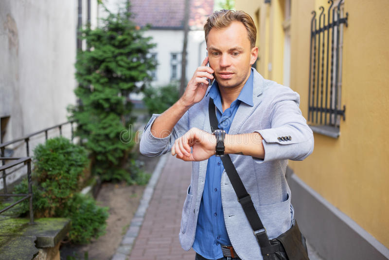 Άτομο που ελέγχει το χρόνο στο ρολόι του και που μιλά στο τηλέφωνο στοκ φωτογραφίες με δικαίωμα ελεύθερης χρήσης