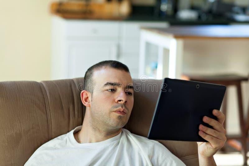 Άτομο που διαβάζει έναν υπολογιστή ταμπλετών στοκ φωτογραφία