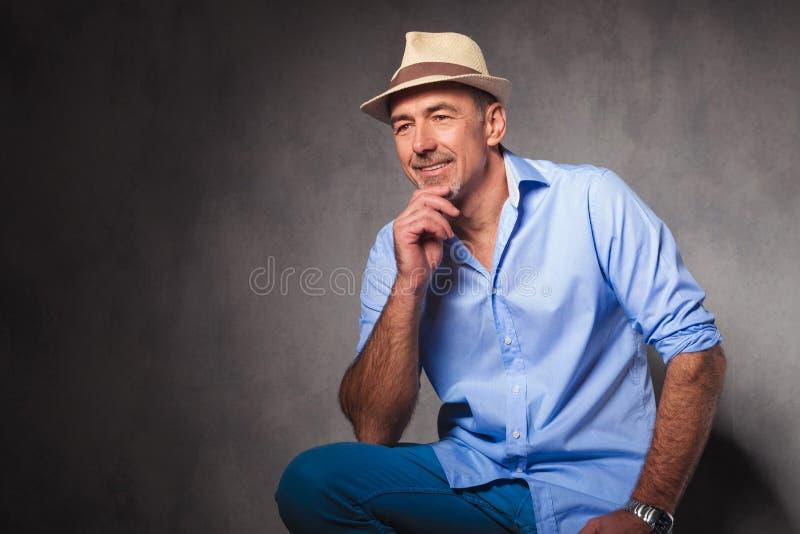 Άτομο που κάθεται ώριμο στο υπόβαθρο στούντιο που κοιτάζει μακριά στοκ εικόνα