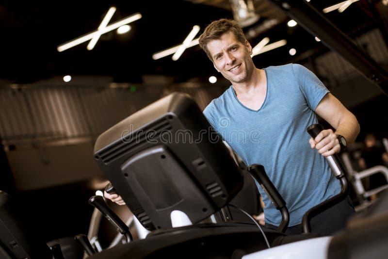 Άτομο που κάνει την άσκηση στον ελλειπτικό διαγώνιο εκπαιδευτή στη λέσχη γυμναστικής αθλητικής ικανότητας στοκ φωτογραφία με δικαίωμα ελεύθερης χρήσης