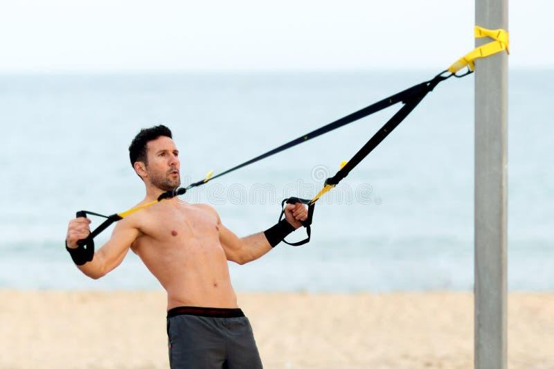 άτομο που κάνει τη θωρακική trx άσκηση στην παραλία στοκ φωτογραφία