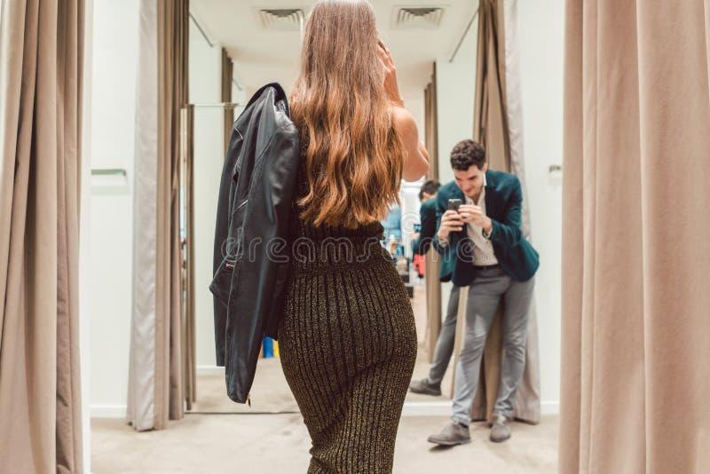 Άτομο που κάνει τη φωτογραφία της συζύγου του με το νέο φόρεμά της στο κατάστημα μόδας στοκ εικόνες