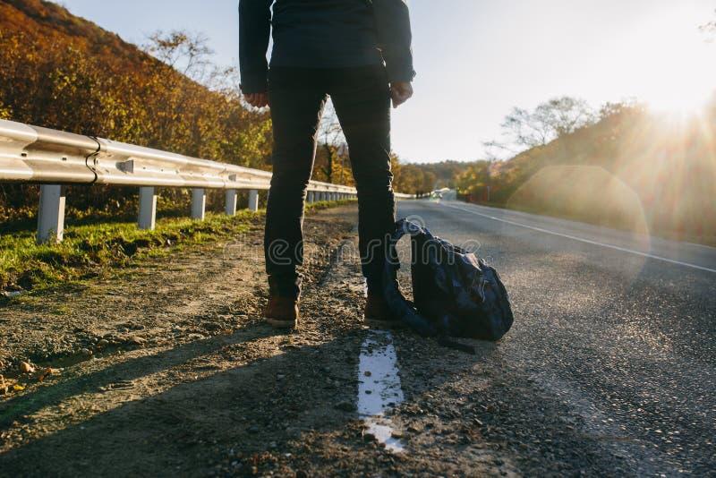 Άτομο που κάνει ωτοστόπ σε μια εθνική οδό Ταξιδιώτης που παρουσιάζει αντίχειρα επάνω επάνω για να κάνει ωτοστόπ κατά τη διάρκεια  στοκ εικόνα με δικαίωμα ελεύθερης χρήσης