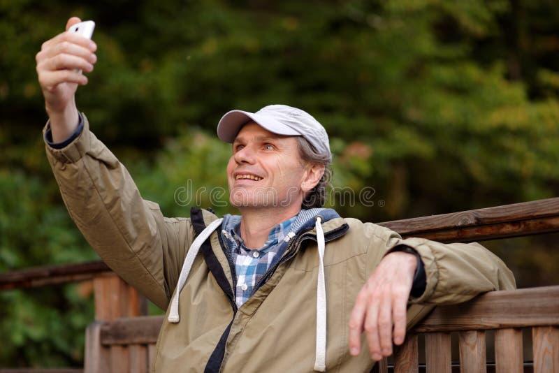 Άτομο που κάνει selfie χρησιμοποιώντας το κινητό τηλέφωνο στοκ εικόνες