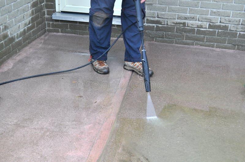Άτομο που καθαρίζει ένα πεζοδρόμιο με ένα πλυντήριο πίεσης κατά τη διάρκεια του ναυπηγείου άνοιξη και της εργασίας κήπων στοκ φωτογραφίες