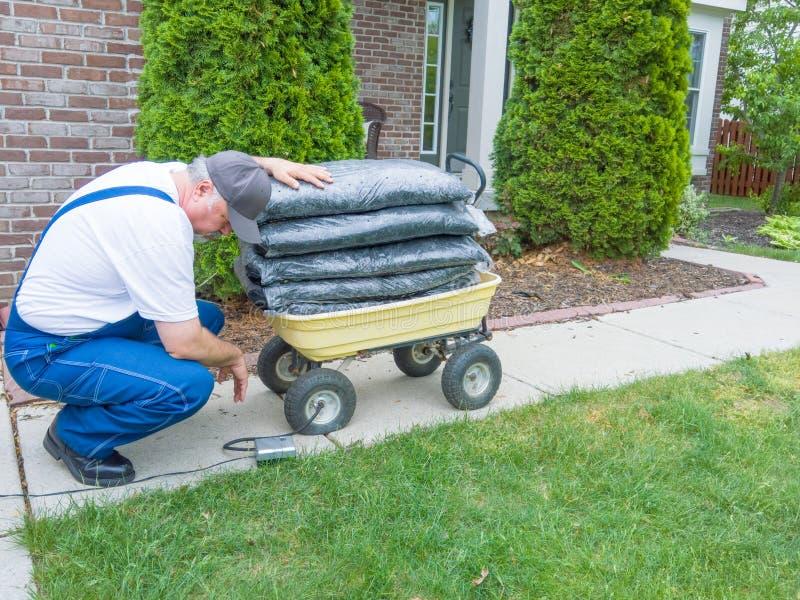 Άτομο που καθορίζει μια οπή wheelbarrow στοκ εικόνες