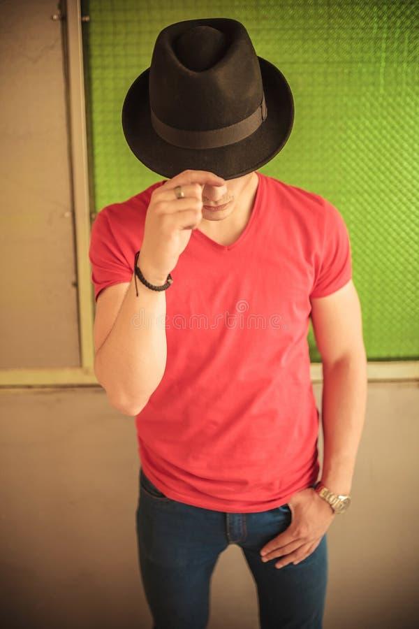 Άτομο που καλύπτει το πρόσωπό του με το καπέλο στοκ εικόνες