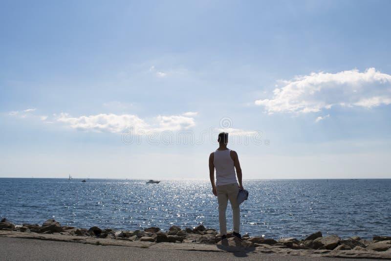 Άτομο που κοιτάζει έξω πέρα από τον ωκεανό μια καυτή και ηλιόλουστη θερινή ημέρα στοκ φωτογραφία