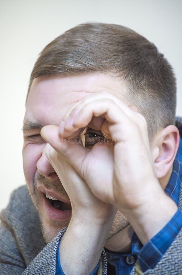 Άτομο που κοιτάζει μέσω των δάχτυλων όπως μέσω του φανταστικού τηλεσκοπίου στοκ εικόνα με δικαίωμα ελεύθερης χρήσης