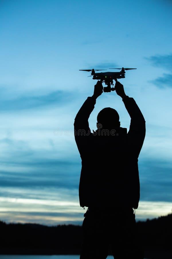 Άτομο που κρατά έναν κηφήνα για την αεροφωτογραφία Σκιαγραφία ενάντια στο τ στοκ εικόνες