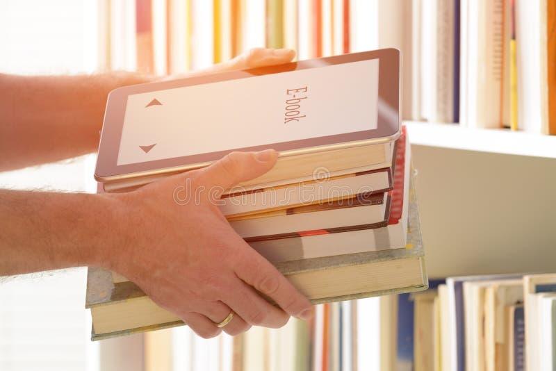 Άτομο που κρατά έναν σύγχρονο αναγνώστη και τα βιβλία ebook στοκ εικόνα