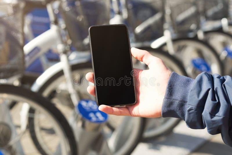 Άτομο που κρατά ένα κινητό τηλέφωνο κοντά στο σταθμό ποδηλάτων στοκ φωτογραφία