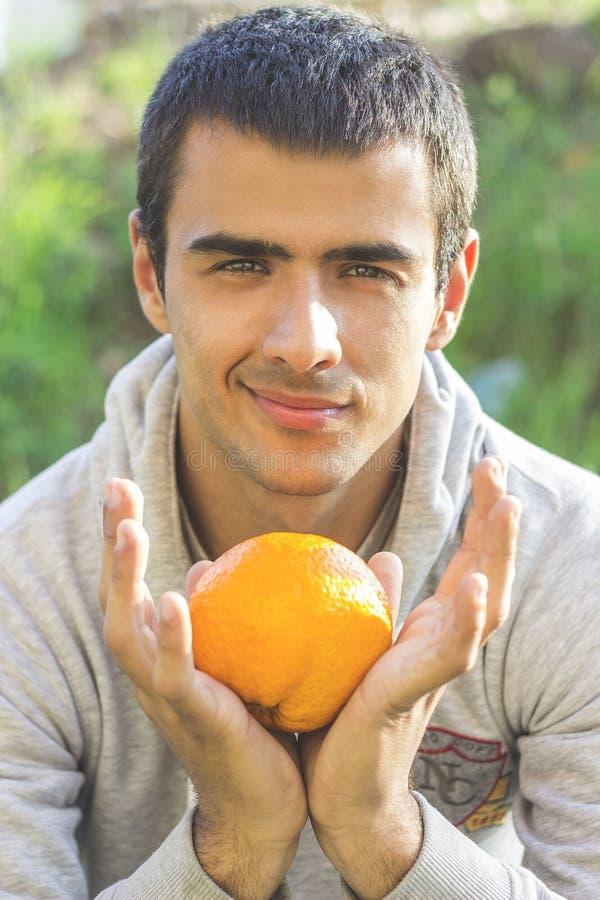 Άτομο που κρατά ένα πορτοκάλι στοκ εικόνες με δικαίωμα ελεύθερης χρήσης
