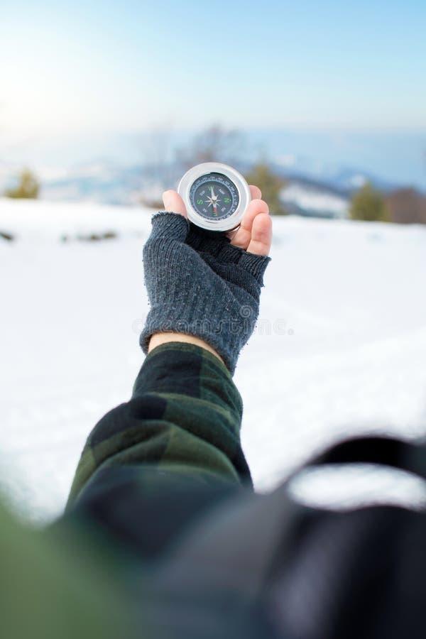 Άτομο που κρατά μια πυξίδα μετάλλων στο βουνό στοκ εικόνα με δικαίωμα ελεύθερης χρήσης