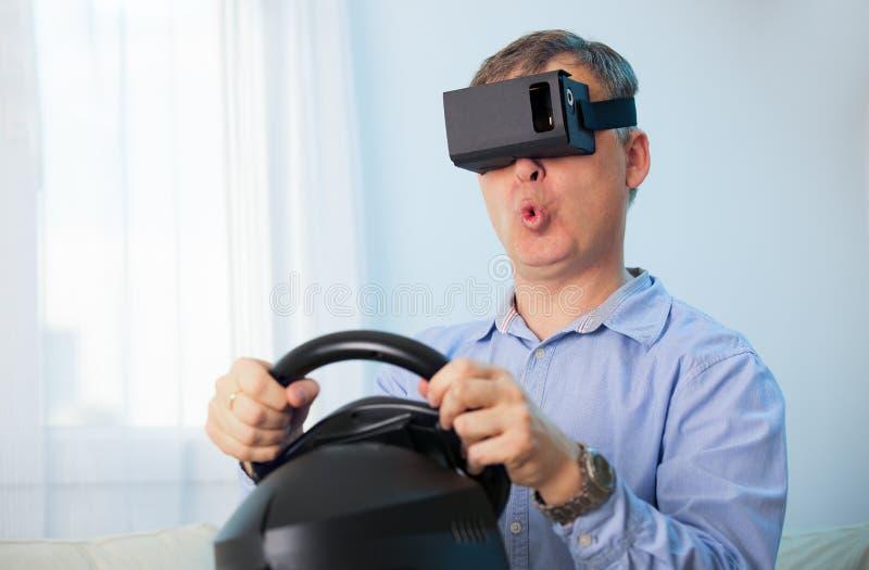Άτομο που κρατά μια ρόδα υπολογιστών τυχερού παιχνιδιού που παίρνει την εμπειρία που χρησιμοποιεί τα γυαλιά VR-κασκών στοκ φωτογραφία με δικαίωμα ελεύθερης χρήσης