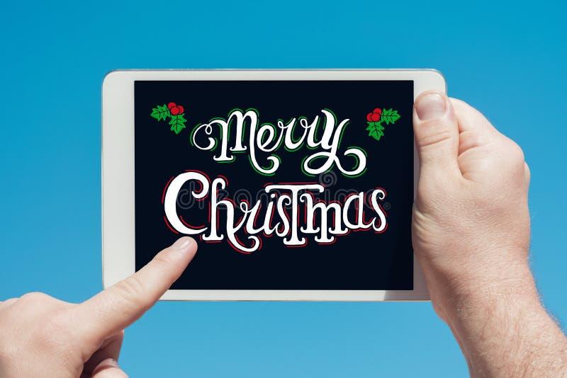 Άτομο που κρατά μια συσκευή ταμπλετών με τη Χαρούμενα Χριστούγεννα ` κειμένων ` στοκ εικόνα με δικαίωμα ελεύθερης χρήσης