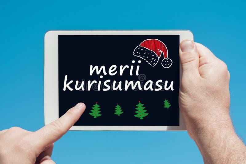 Άτομο που κρατά μια συσκευή ταμπλετών με το κείμενο στην ιαπωνική Χαρούμενα Χριστούγεννα ` Merii Kurisumasu ` στοκ εικόνες