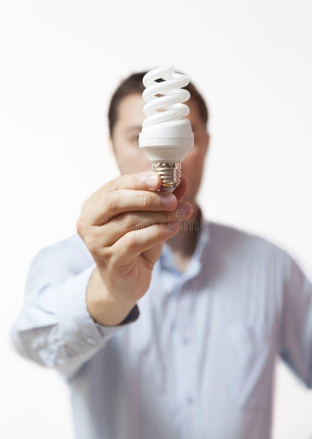 Άτομο που κρατά μια φιλική λάμπα φωτός eco στοκ εικόνες με δικαίωμα ελεύθερης χρήσης