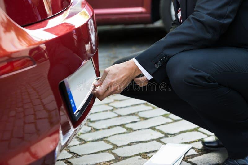 Άτομο που κρατά τον κενό άσπρο αριθμό πινακίδας αυτοκινήτου στοκ φωτογραφία με δικαίωμα ελεύθερης χρήσης
