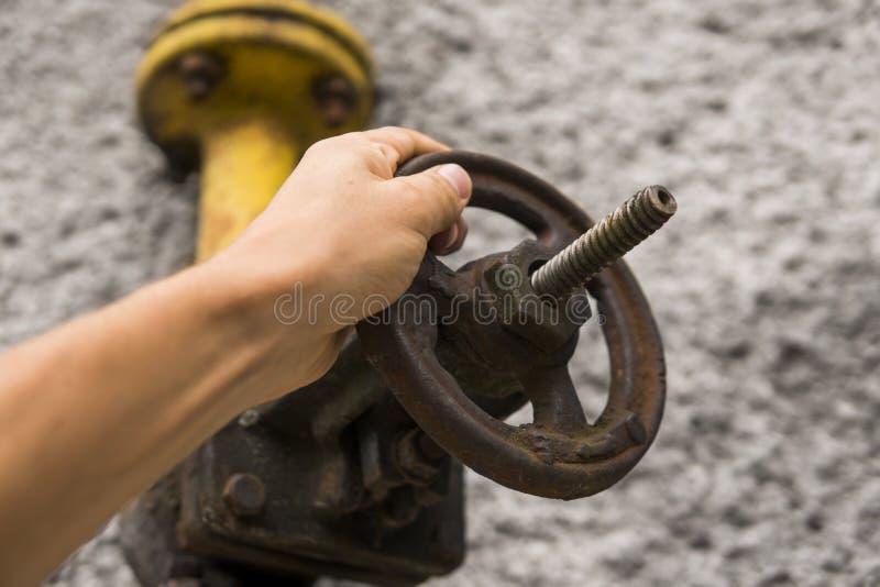 Άτομο που κρατά τον παλαιό ξεπερασμένο γερανό αερίου στο υπόβαθρο ενός γκρίζου τοίχου Η παλαιά πύλη αερίου του κίτρινου χρώματος  στοκ φωτογραφία με δικαίωμα ελεύθερης χρήσης